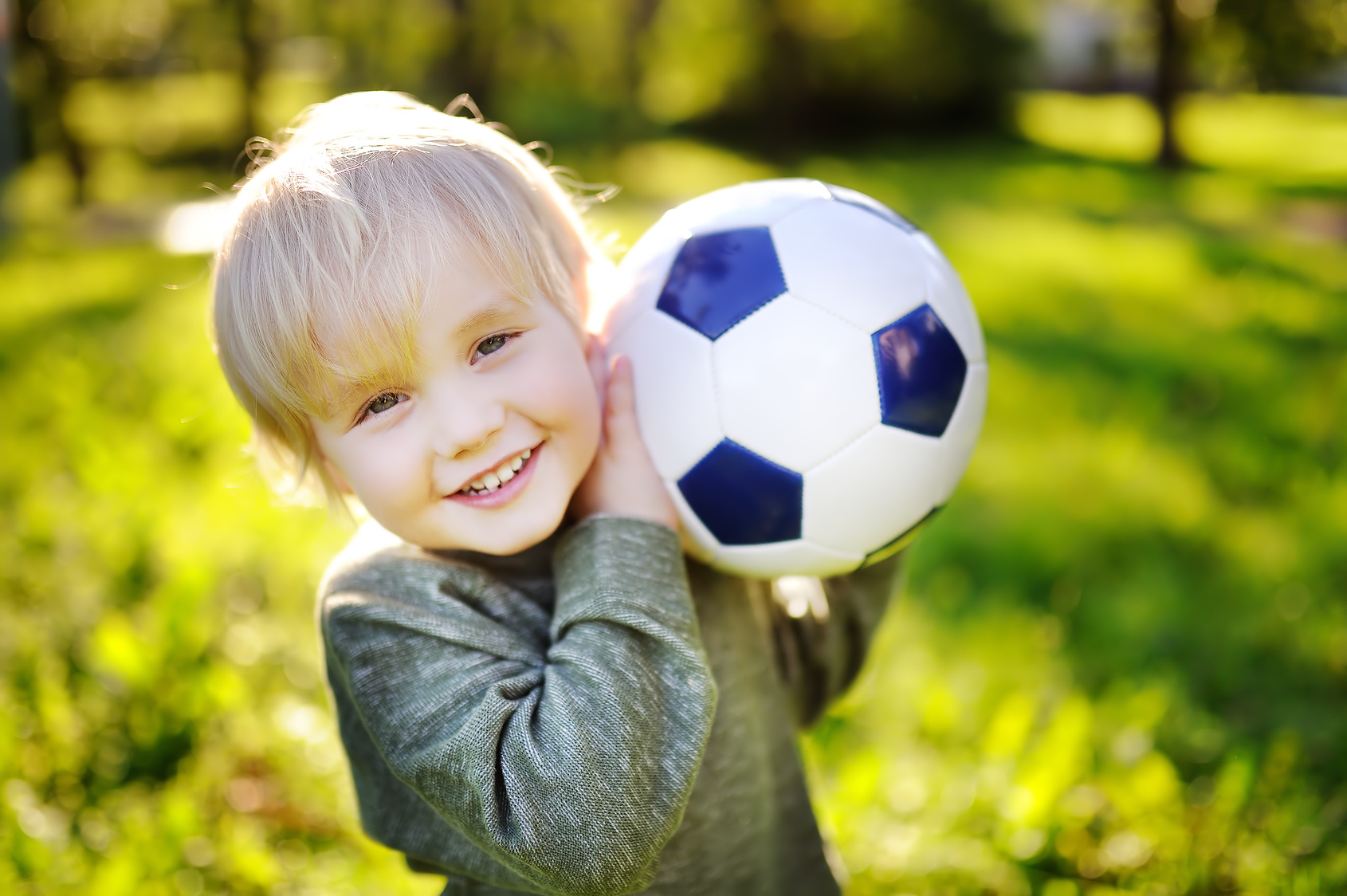 Little boy having fun playing a soccer game on sunny summer day. Active outdoors game for toddler